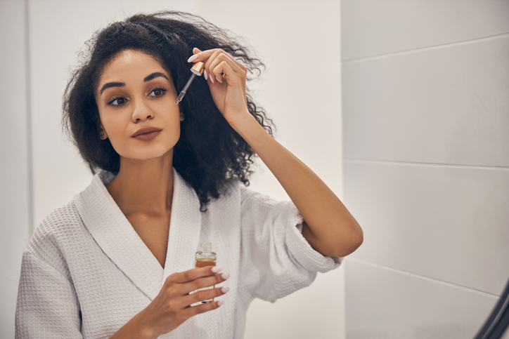 Portrait of a gorgeous woman applying a facial serum to her skin before the mirror