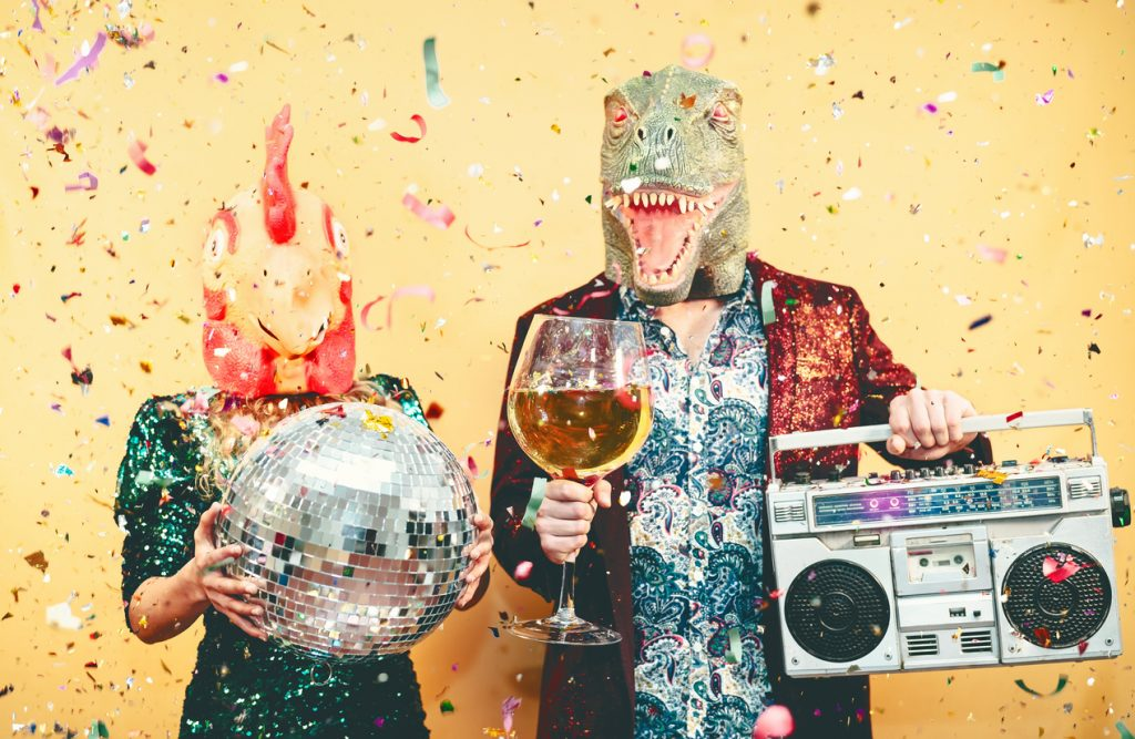 IV Treatments Near Me in Eugene Oregon - Crazy couple celebrating new year eve wearing chicken and dinosaur t-rex mask - Young trendy people having fun drinking champagne and listening music with vintage boombox - Absurd and holidays concept